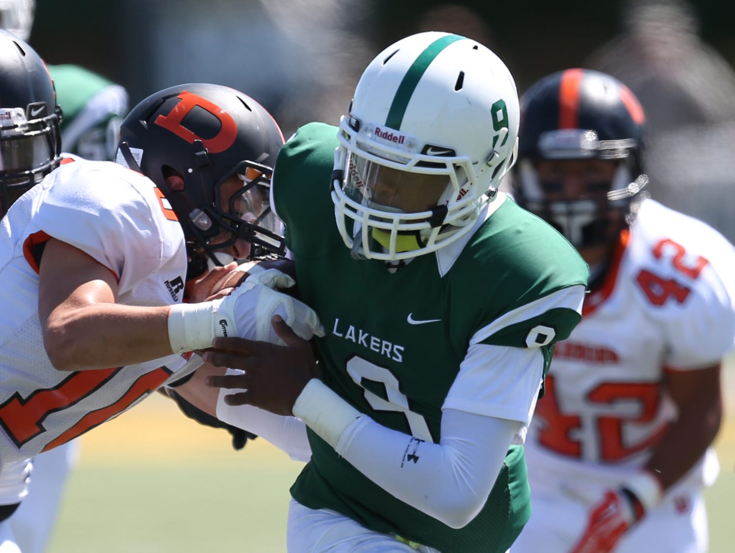 West Bloomfield's Trishton Jackson, right, is tackled by Dearborn's Ahmed Hazime on Aug. 28, 2014, in Detroit.