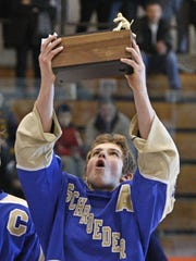 Schroeder assistant captain Billy Van Appledorn holds up the championship trophy after winning the Section V Class B ice hockey championship Sunday, Feb. 23, 2014 at Ritter Arena at RIT in Henrietta.