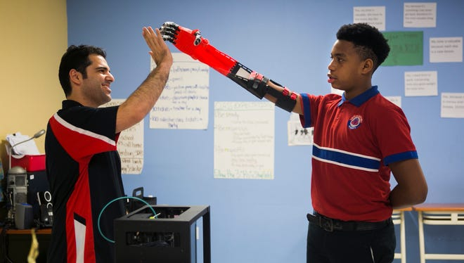 """April 7, 2017 - Dontavius Morris, a 14-year-old eighth grade student at Memphis School of Excellence, high fives his teacher Mehmet Gokcek, a STEM/Project-based learning curriculum developer, after receiving a prosthetic arm at school on Friday. """"It made me feel excited 'cause it's a new thing that I got that's surprising for me to see,"""" Morris said. The school used its 3D printer to make the arm, with a cost between $50-$60, and three months to create."""