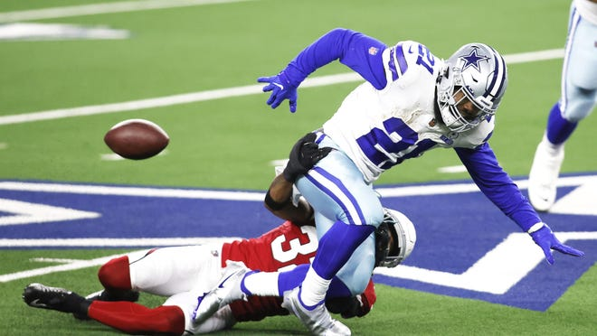 Arizona strong safety Budda Baker (32) causes Dallas running back Ezekiel Elliott (21) to fumble in the first quarter at AT&T Stadium in Arlington on Monday, Oct. 20.