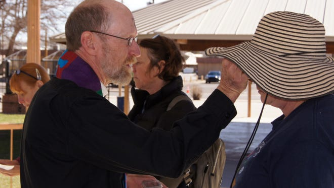 The Rev. Paul Moore, vicar of the Episcopal Church of the Good Shepherd, applies ashes to congregants' foreheads  in Gough Park in Silver City in 2015.  This year both Good Shepherd and the United Church of Christ will be offering the Imposition of Ashes in Gough Park and at the Visitor's Center.