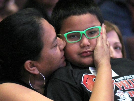 A mother congratulates her son after he exited competition