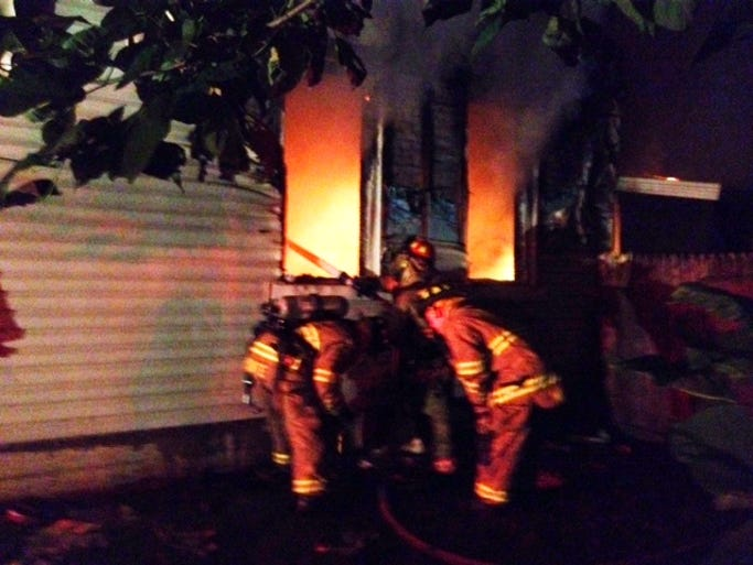 Firefighters work to put out a fire on West Holliday Street on Sunday morning.