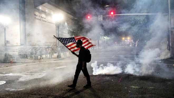 A Black Lives Matter protester carries an American flag as tear gas fills the air outside the Mark O. Hatfield United States Courthouse on Tuesday in Portland.