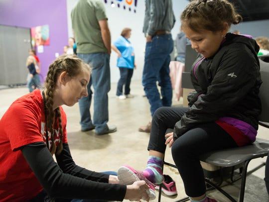 Myelle Harris, left, helps Isabella Huerta,5, try on