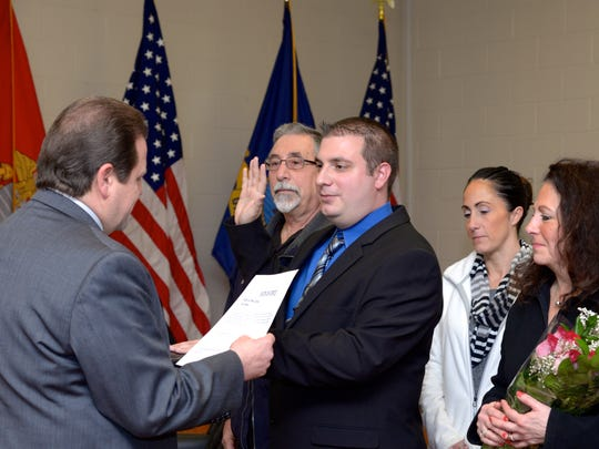 Palisades Park Mayor James Rotundo(left) swears in new police officer Robert DeVito, his family members stood around him, Tuesday, Nov. 22, 2016, in Palisades Park Borough Hall.