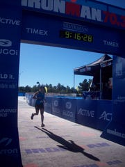 Reporter Beth Roessner crosses the finish like at Ironman 70.3 Silverman, her first half Ironman.