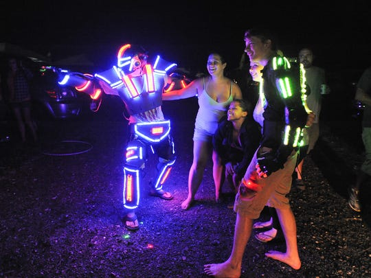 Firefly Music Festival fans pose for a picture with Spencer Bahnsen (left) in his Ultra LED Man suit in 2014.