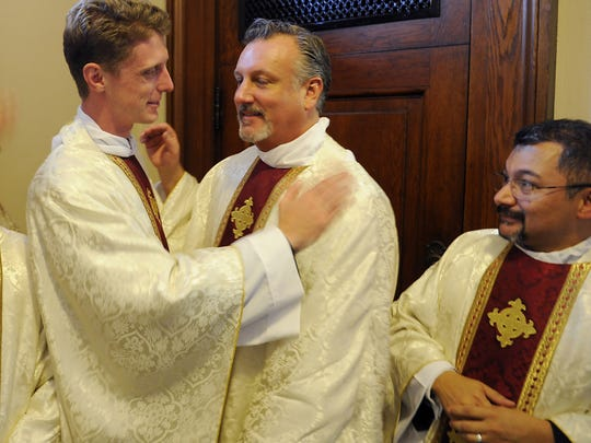 "The Rev. Daniel Reehil, pictured at center following his ordination ceremony in 2014, has attracted controversy following his decision to remove the ""Harry Potter"" books from the library at St. Edward Catholic Schools."