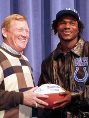 Running back Edgerrin James (right) is presented with a game ball to commemorate his being picked as the Indianapolis Colts' first round selection in the 1999 NFL Draft by Colts president Bill Polian.