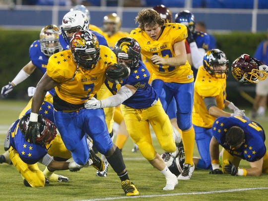 Helmets go flying as Gold's Kani Kane of Sussex Tech (left) is caught by Blue's Dennis Robinson of Caravel in the second half of the DFRC Blue-Gold game at Delaware Stadium in 2015.