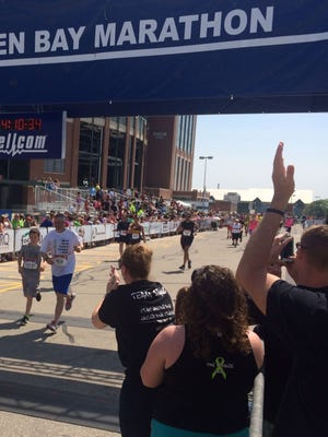 Chuck Spang of De Pere and his 13-year-old son, Owen, cross the finish line together outside Lambeau Field in the 17th annual Cellcom Green Bay Marathon as family members cheer off to the side Sunday, May 22, 2016. Spang finished the full marathon in 4 hours, 4 minutes, 23 seconds, a year after he was diagnosed with lymphoma.