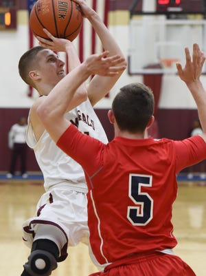 Arlington's Drew Whiteley takes a shot as Ketcham's Luke Tebold covers him during Tuesday's game at Arlington.