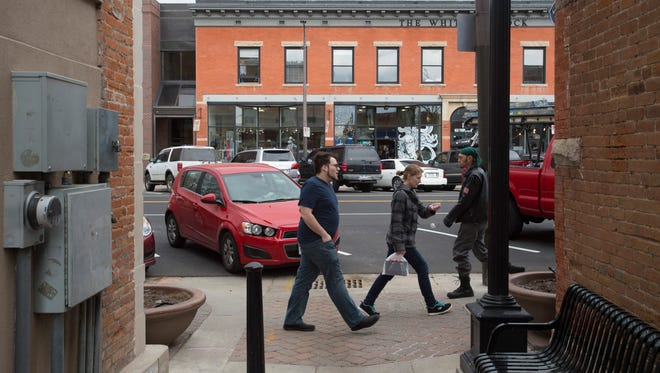 People walk down Walnut Street in Old Town on Thursday, March 15, 2018.