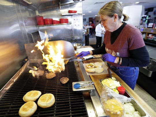 Drift Inn staff member Lori Miller cooks burger patties