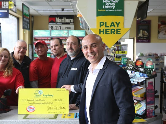 Ameer Krass, owner of Riverdale Lukoil South, poses for a picture with some of his employees  April 2, 2018. The most valuable lottery ticket in New Jersey state history was sold at his store. The drawing for $535 million was held March 30. Krass received a check for $30,000 which he said he will use for bonuses for his employees and donate to a charity. The winner wouldn't come forward for another 11 days.