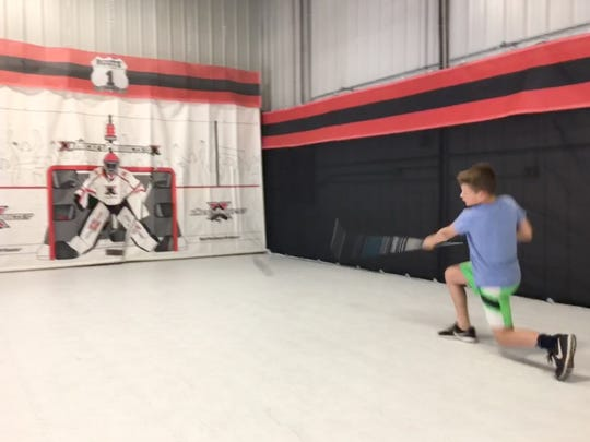 A student takes shooting practice at a trainer at Route 1 Hockey. The Ashwaubenon business provides offseason training opportunities for hockey players.