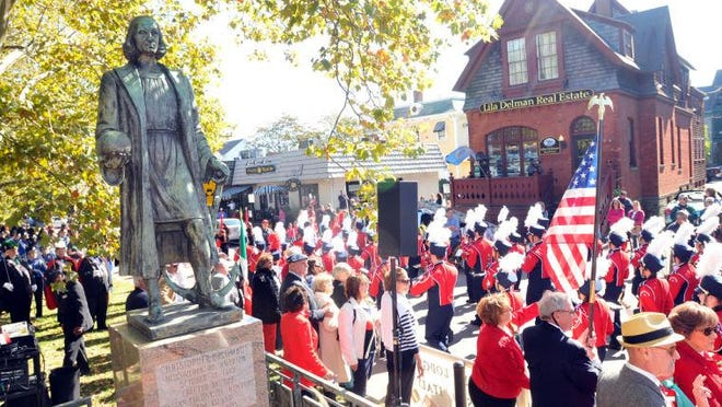 Spectators watch the conclusion of the Columbus Day Parade near the Christopher Columbus statue on Memorial Boulevard in Newport.