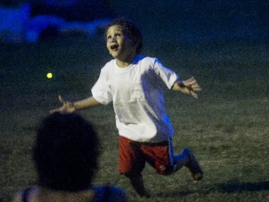 Noah Patterson, 3, of York, chases fireflies during the showing of Nanny McPhee Returns at Kiwanis Lake as part of the York City Recreation and Parks 2011 Summer Movie Series Wednesday, Jule 6, 2011. DAILY RECORD/SUNDAY NEWS - KATE PENN