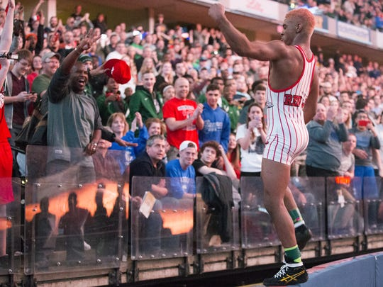 New Palestine's Chad Red  hops on a wall to greet fans after he beat also-undefeated wrestler Nick Lee of Evansville Mater Dei at the IHSAA Wrestling State Finals at Bankers Life Fieldhouse, Feb. 20, 2016.