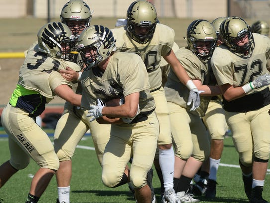 Oak Park's Bryce Hardy carries the ball before a scrimmage