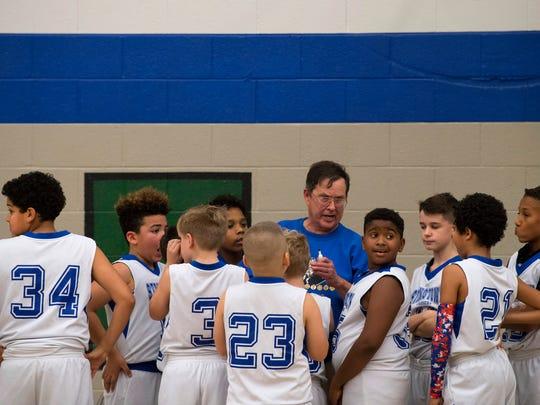 Stringtown Elementary School gym teacher Jim Schmidt coaches his 5th-grader boys basketball team at halftime against Highland Thursday night, Jan. 8, 2018. Schmidt coaches both the boys and girls teams.