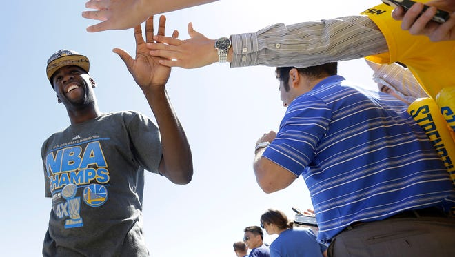 Golden State Warriors forward Draymond Green, left, high fives team employees after the team landed in Oakland, Calif., on Wednesday.