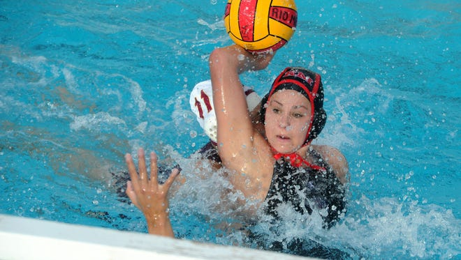 Rio Mesa's Kayla Wallace scores while being guarded by Oxnard's Madison Behrens in the first half of Wednesday's water polo match at Rio Mesa High.