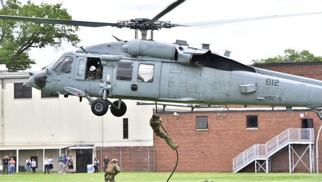 Marines rope down from a helicopter landing at Garfield High School for a mine countermeasures demonstration, as a part of Fleet Week on Friday.