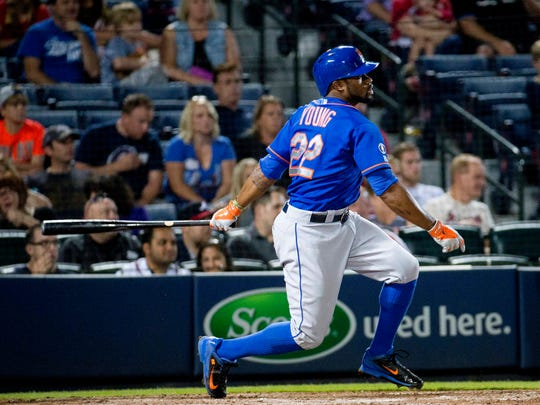 The New York Mets' Eric Young Jr. follows through with a two-run base hit in the ninth inning of a 2014  game against the Atlanta Braves in Atlanta. New York won 5-0.