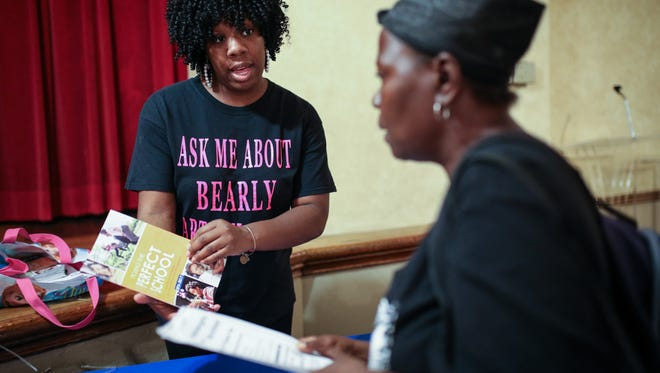 DPS Ambassador Jeannette Washington, 28, of Detroit hands out information about schools, DPS programs, a free T-shirts to Lisa Early, 46, of Detroit, during a back-to-school fair at the Historic Little Rock Baptist church in Detroit, on Monday, Aug. 29, 2016.