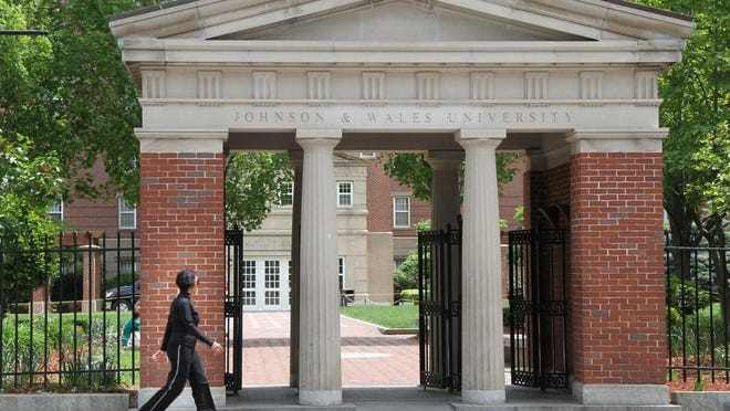 A pedestrian walks by the gates to the Johnson & Wales Downtown Providence Campus on Weybosset Street.