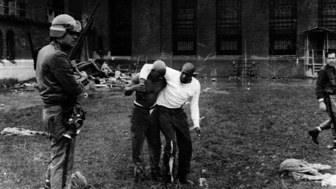 One prisoner helps another hobble from the field of carnage within Attica Correctional Facility on Sept. 13, 1971, the day state troopers were sent in to retake the prison and 39 people were killed.