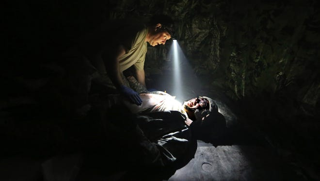"""Former combat medic Troy Reihsen tells a wounded soldier, Jordan Gonzalez, also a former medic, """"You're not going to die"""" as he works Tuesday to stabilize the """"patient"""" at the University of Washington's lab simulation."""