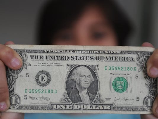 A person holds a one dollar bill on Dece