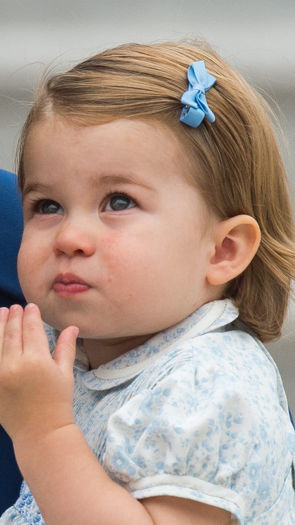 Princess Charlotte of Cambridge wore a print frock and a blue bow in her hair.