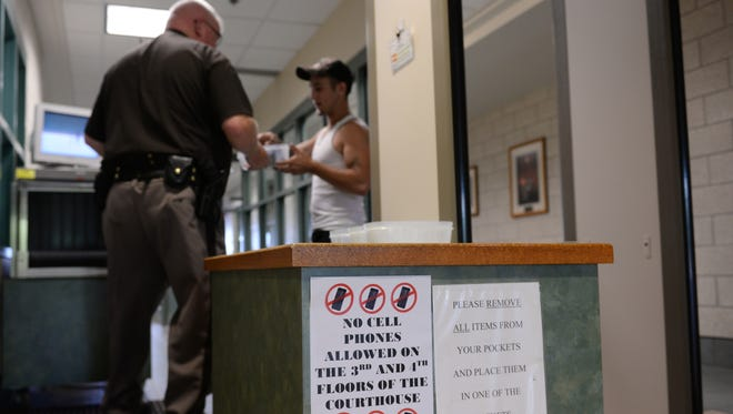 Deputy Rodney Beals hands back items to a man who passed through a metal detector on Thursday, June 30, 2016 at the Clinton County Courthouse in St. Johns. The courthouse has a ban on cell phones on the third and fourth floors.