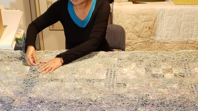 "McPherson artist Shin-hee Chin works on a fiber art piece titled ""Song of the Sea-shore."""