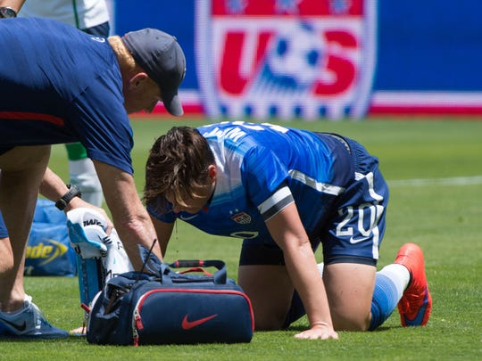 USA forward Abby Wambach (20) is looked at by a team trainer with a bloody nose after a collision during the second half against Ireland.