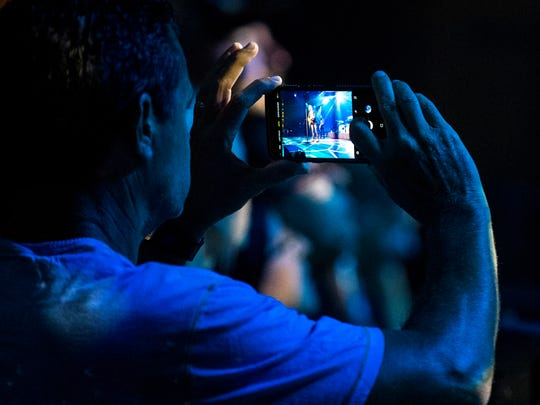 A fan records Dierks Bentley as he performs during