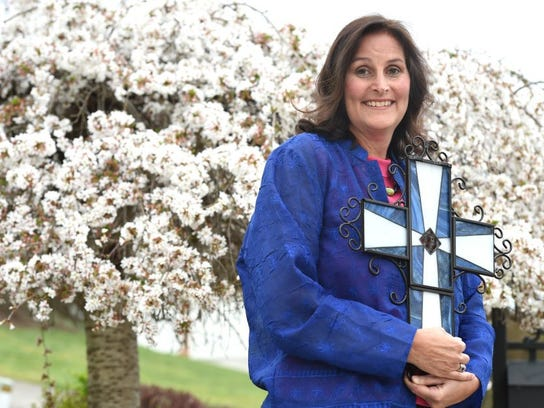 Michelle Ironside Henry, holding a stained-glass cross