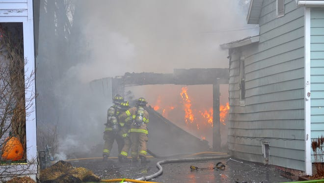 Oconto firefighters work to extinguish a fire in a garage at 102 Center St., in Oconto. The blaze spread to the home, as well as the home at left.