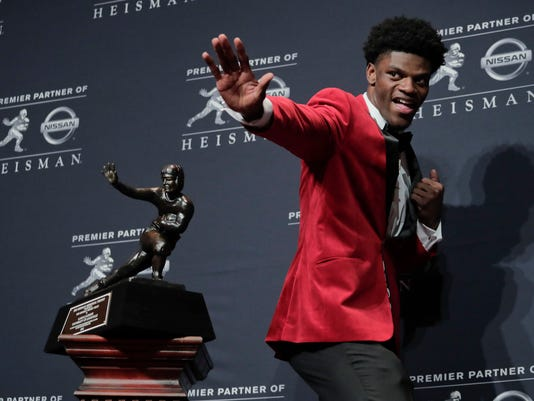 FILE - In this Dec. 10.2016, file photo, Louisville's Lamar Jackson poses with the Heisman Trophy after winning the Heisman Trophy award in New York. The ACC returns the Heisman Trophy winner and the defending national champion, and has two top-five teams in the national polls. Collectively, they've helped make the conference even more attractive to fans and viewers _ starting with a list of opening-week matchups that include Florida State-Alabama, Virginia Tech-West Virginia and Georgia Tech-Tennessee. (AP Photo/Julie Jacobson, File)