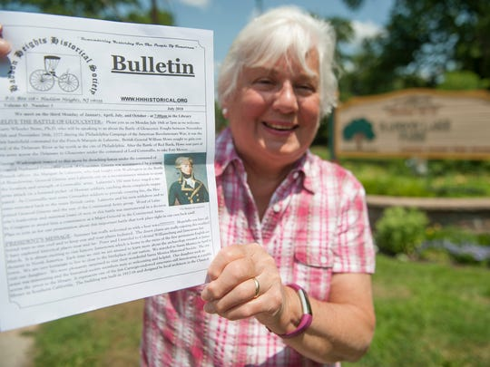 Haddon Heights Historical Society President Elena Hill displays a bulletin announcing that a presentation on the Battle of Gloucester will be held at the Haddon Heights Library on Monday, July 16th, as Hill stands near Haddon Lake Park in Haddon Heights, near the location of where the battle took place.
