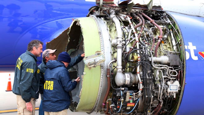 National Transportation Safety Board investigators examine damage to the engine of the Southwest Airlines plane that made an emergency landing at Philadelphia International Airport in Philadelphia on April 17, 2018.