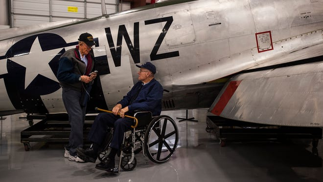 World War II Army Air Corp veterans Philip Daily (left) and Lee Bashor talk next to a Republic P47D-40 Thunderbolt fighter plane on May 5, 2018, at the National Museum of World War II Aviation in Colorado Springs, Colorado.