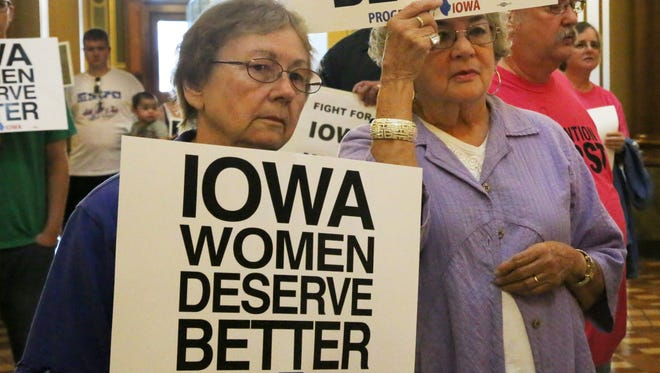 Betty Houf of Des Moines, Iowa, and Donna Fleming of Beaverdale, hold signs during the Iowa Women Deserve Better Rally at the State Capitol in Des Moines on Wednesday.