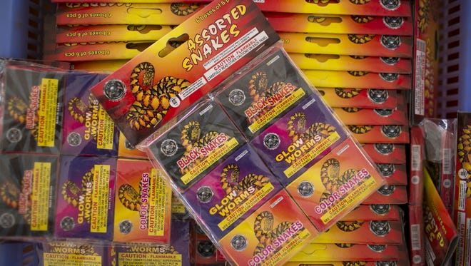 Fireworks sit for sale on a table at Red Hot Fireworks stand on Tuesday, June 28, 2016, in Phoenix, Ariz.