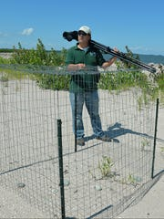 "Josh Martinez, a DNR wildlife biologist, explains the purpose of a wire ""exclosure"" that protected a family of piping plovers from predators on Cat Island in lower Green Bay."