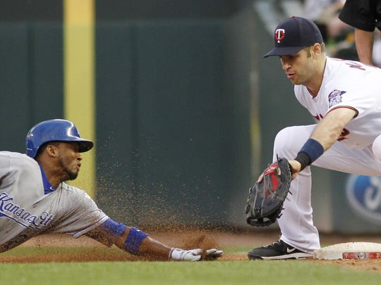 Minnesota Twins first baseman Joe Mauer catches the ball on a pick-off play on the Kansas City Royals' Alcides Escobar, who was safe in the fourth inning Tuesday in Minneapolis.